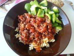 Eilisen illallinen: jauhelihakastiketta ja pastaa. Vierellä kasa sämpylöitä.