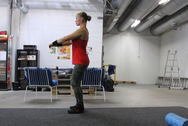 Airsquat. Alkuasennossa taakreidet taakse, hartiat taakse, vatsa ja pylly tiukkana.